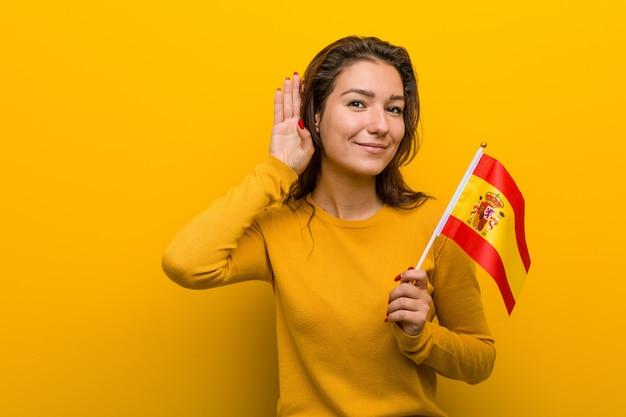 Giovane donna europea che tiene una bandiera spagnola che prova ad ascoltare un gossip.