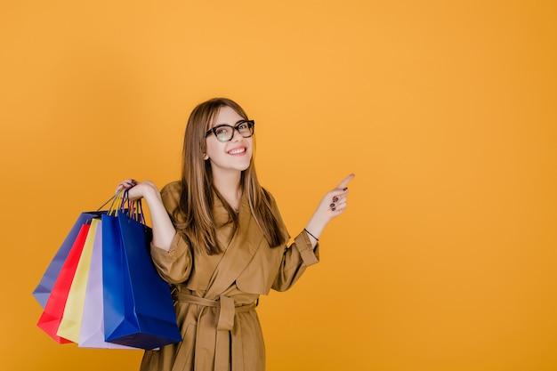 Giovane donna europea dei pantaloni a vita bassa in vetri e cappotto con i sacchetti della spesa variopinti isolati sopra giallo