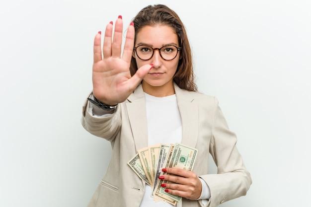 Giovane donna europea di affari che tiene le banconote del dollaro che stanno con il fanale di arresto di rappresentazione della mano stesa, impedendovi.