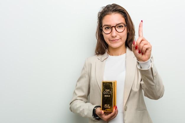 Giovane donna europea di affari che tiene un lingotto d'oro che mostra il numero uno con il dito.