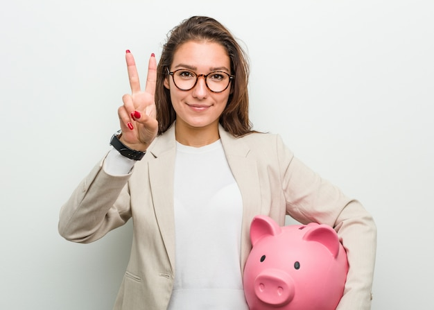 Giovane donna europea di affari che tiene un porcellino salvadanaio che mostra numero due con le dita.