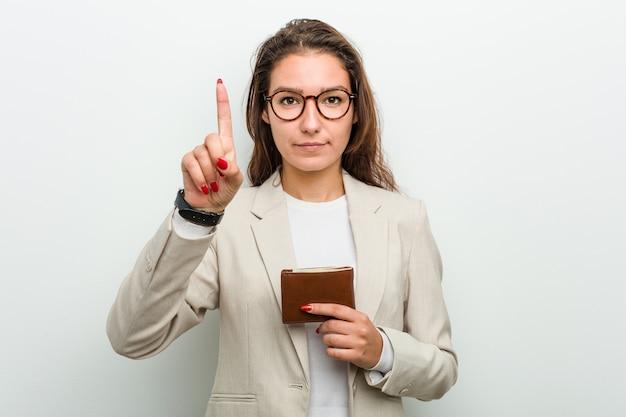 Giovane donna europea di affari che tiene un portafoglio che mostra numero uno con il dito