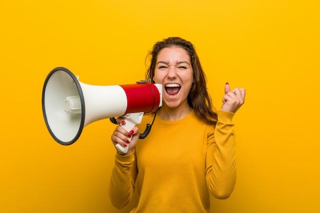 Giovane donna europea in possesso di un megafono che celebra una vittoria o un successo