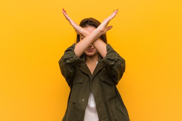 Giovane donna europea isolata sopra giallo che tiene due armi attraversate, concetto di rifiuto.