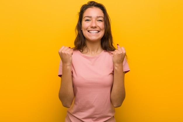 Giovane donna europea isolata su sfondo giallo tifo spensierata ed eccitata. concetto di vittoria