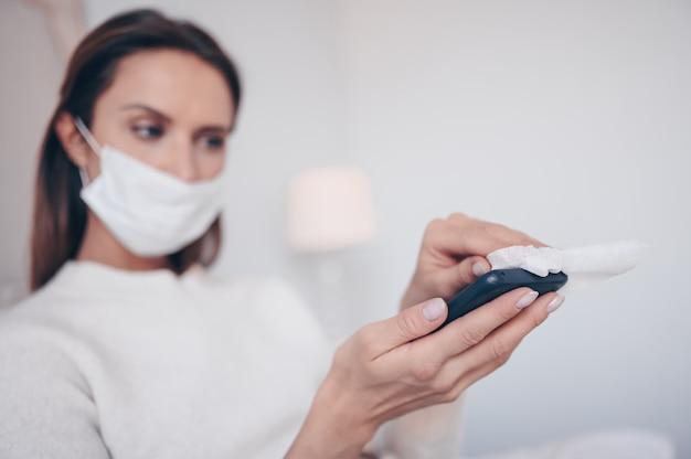 Giovane donna europea nella maschera in camera da letto con il computer portatile durante l'isolamento del coronavirus