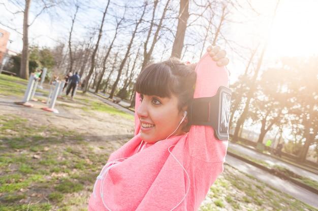 Giovane donna facendo braccia e spalle stretching esercizi.