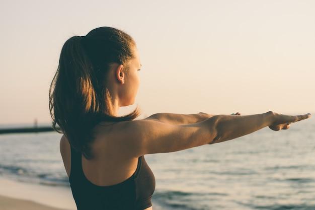 Giovane donna facendo esercizi di mattina in spiaggia