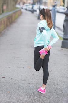 Giovane donna facendo esercizi di stretching prima di fare jogging.