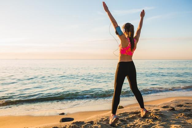 Giovane donna facendo esercizi sportivi sulla spiaggia di alba al mattino