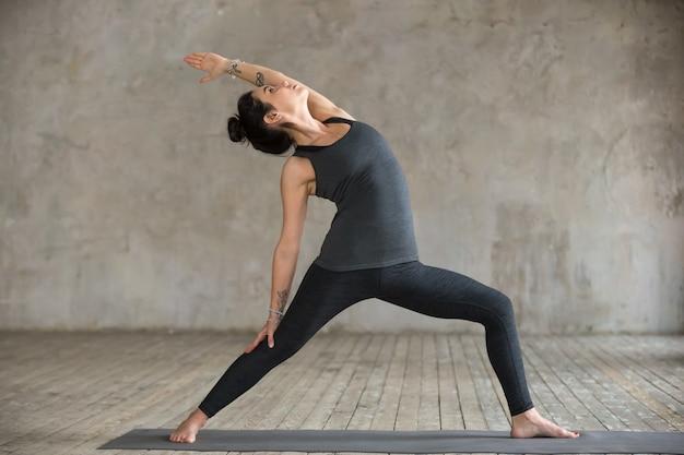 Giovane donna facendo esercizio reverse warrior