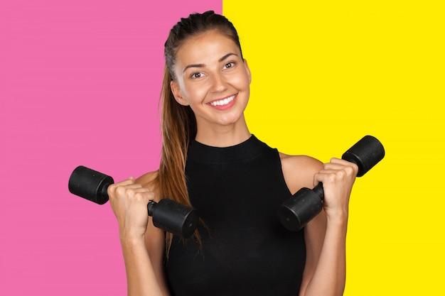 Giovane donna facendo un allenamento di fitness con manubri