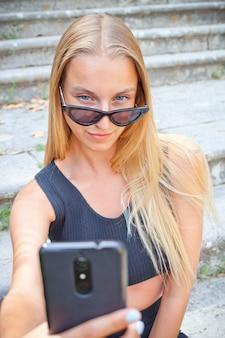 Giovane donna felice attraente che prende selfie sulla città antica