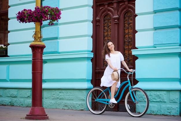Giovane donna felice attraente che sorride allegro che si siede sulla sua bicicletta che riposa dopo il riciclaggio