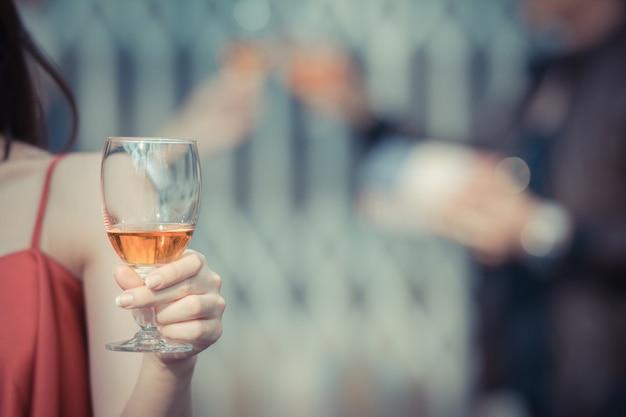 Giovane donna felice bere tenendo e bere un bicchiere di alcol al bar notturno o night club