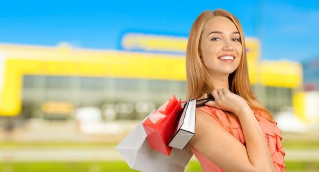 Giovane donna felice caucasica con i sacchetti della spesa