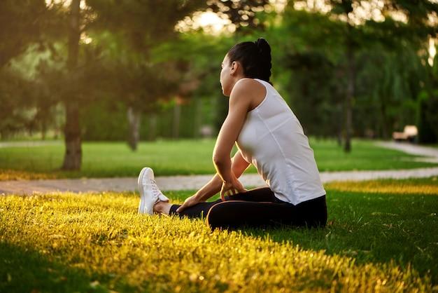 Giovane donna felice che allunga prima di correre all'aperto. la bella ragazza di sport nel parco è impegnata nella forma fisica