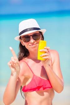 Giovane donna felice che applica lozione solare sul suo naso sulla spiaggia bianca