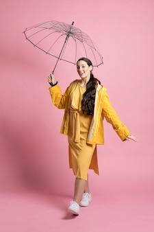 Giovane donna felice che cammina mentre si tiene un ombrello