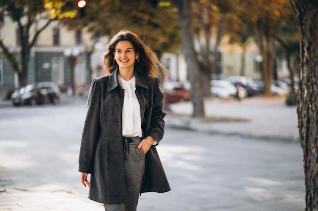 Giovane donna felice che cammina per strada