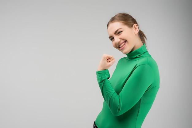 Giovane donna felice che esamina la macchina fotografica con cleanch il pugno alto e sorridente