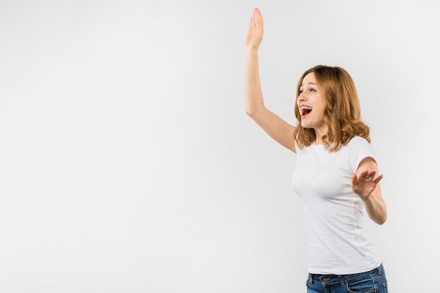 Giovane donna felice che fluttua la sua mano isolata sopra priorità bassa bianca