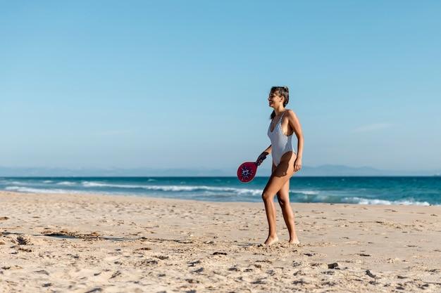 Giovane donna felice che gioca a tennis sulla spiaggia