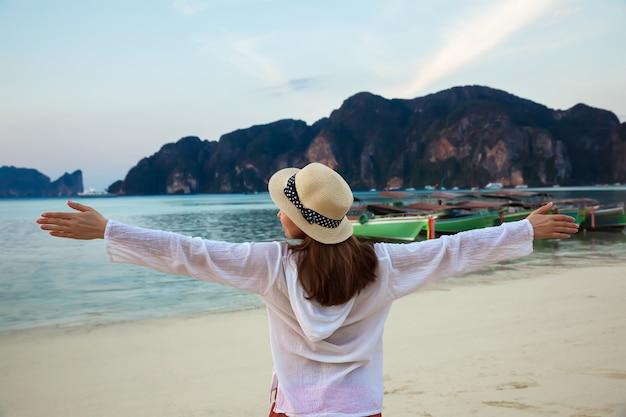 Giovane donna felice che gode del sorgere del sole su un'isola tropicale. tailandia