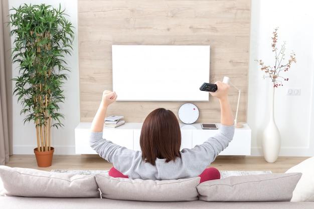 Giovane donna felice che guarda la partita emozionante di sport di calcio della televisione o il concorso della tv