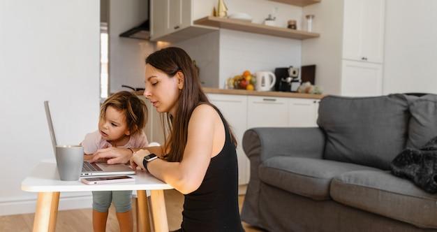 Giovane donna felice che lavora da casa con il bambino. ufficio a casa. quarantena