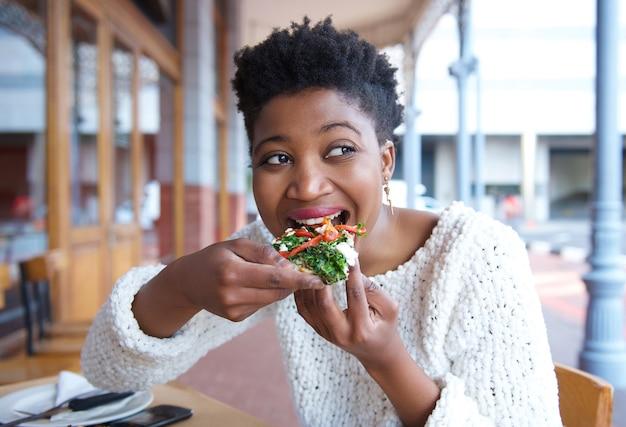 Giovane donna felice che mangia pizza al ristorante
