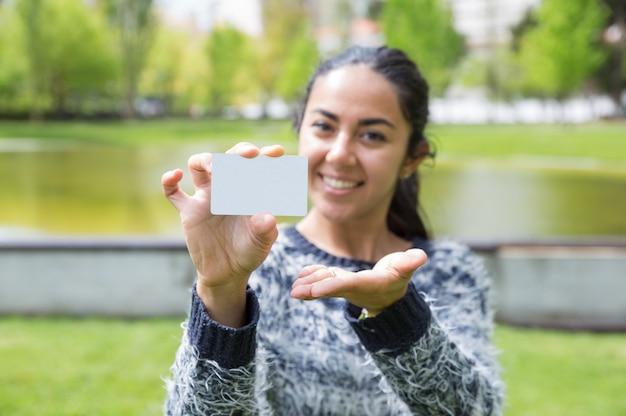 Giovane donna felice che mostra biglietto da visita in bianco nel parco della città