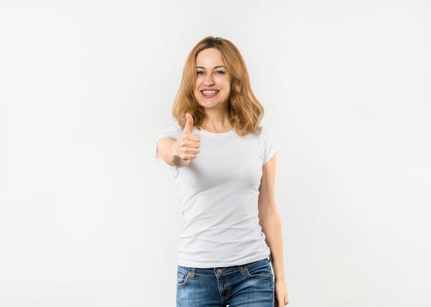 Giovane donna felice che mostra pollice sul segno che guarda alla macchina fotografica contro fondo bianco