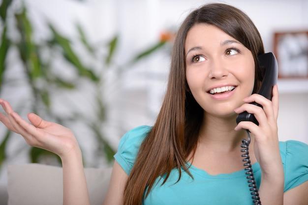 Giovane donna felice che parla sul telefono a casa.