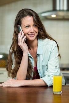Giovane donna felice che parla sul telefono cellulare in cucina