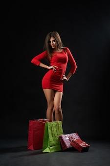 Giovane donna felice che posa con i sacchetti della spesa