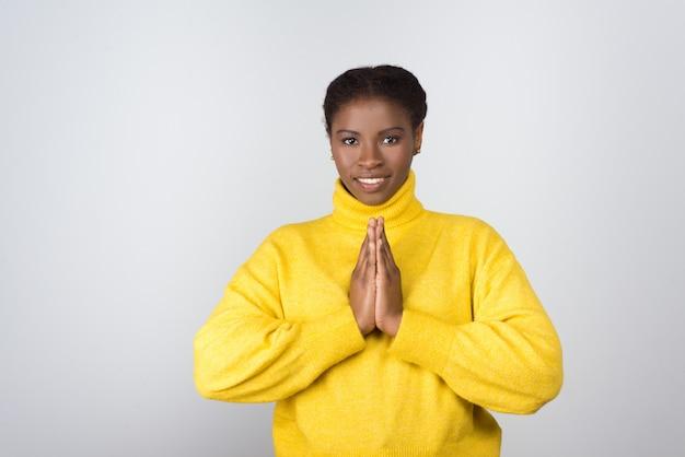 Giovane donna felice che prega e che osserva