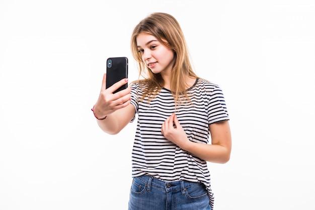 Giovane donna felice che prende le immagini di se stessa allo smart phone, sopra la parete bianca