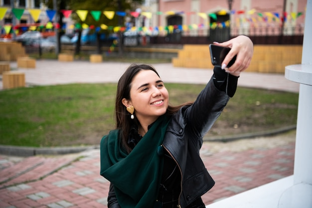 Giovane donna felice che prende selfie. donna che prende la foto del selfie con uno smarphone nella città.