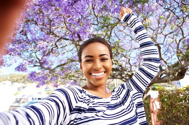 Giovane donna felice che prende selfie fuori con il braccio alzato