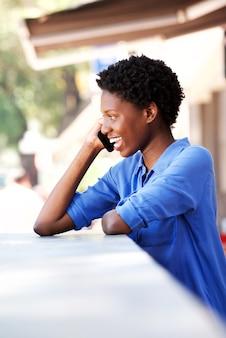 Giovane donna felice che ride e che parla sul telefono cellulare al caffè all'aperto