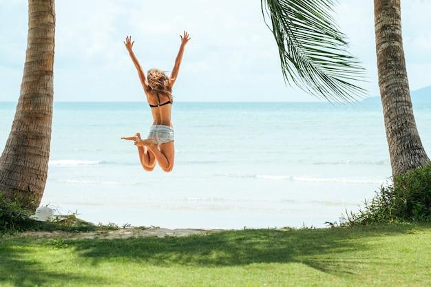 Giovane donna felice che salta sulla spiaggia