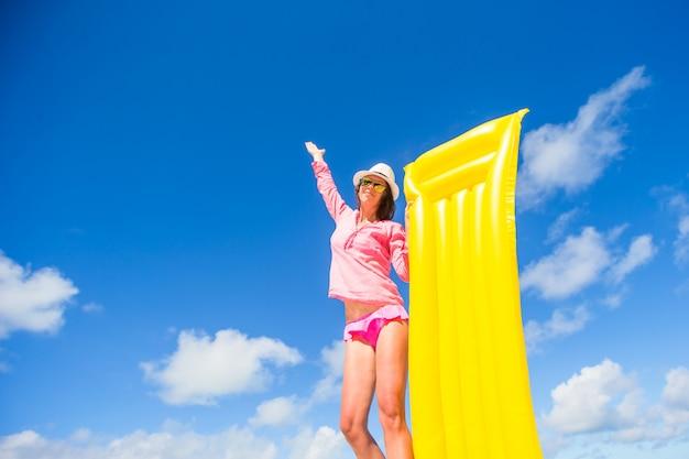 Giovane donna felice che si distende con il materasso di aria sulla spiaggia