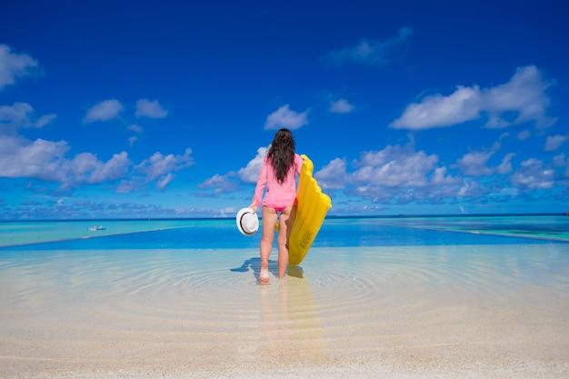 Giovane donna felice che si rilassa con il materasso di aria durante la vacanza tropicale