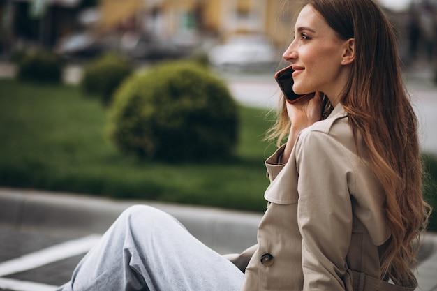 Giovane donna felice che si siede nel parco e che parla al telefono