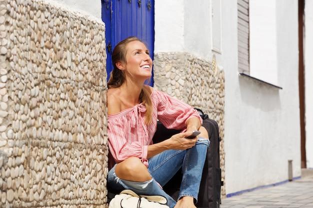 Giovane donna felice che si siede sul marciapiede con la valigia e cellulare