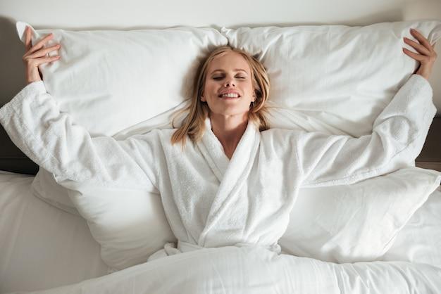 Giovane donna felice che si trova sul grande letto bianco