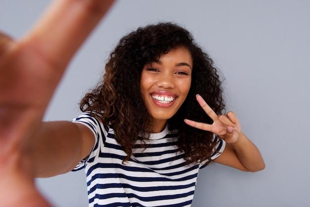 Giovane donna felice che sorride e che prende selfie