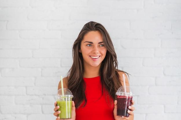 Giovane donna felice che sta contro i frullati della tenuta della parete in tazza di plastica