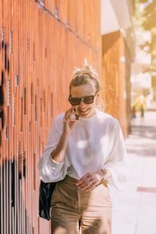 Giovane donna felice che sta sulla via che parla sul telefono cellulare